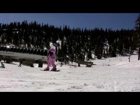 Bambina di un anno con lo snowboard