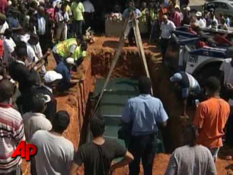 car being lowererd into grave