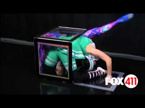 Two Big Apple Circus contortionists squeeze into a small box