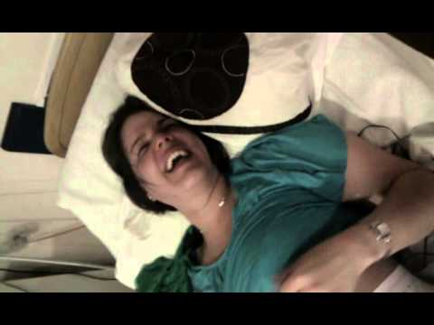 Woman having fun in labor. Laughing hysterically on gas and air.
