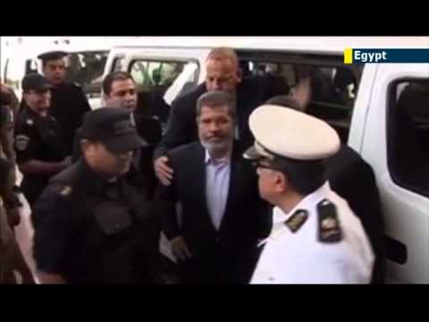Jailed ex-Egyptian President Mohammed Morsi dons convict uniform and smiles in prison mugshot