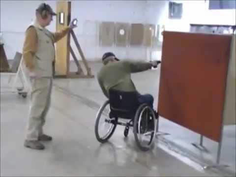 На инвалидной коляске с пистолетом в руках.