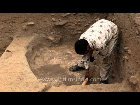 Man sweeping off the loose soil during excavation at Purana Qila