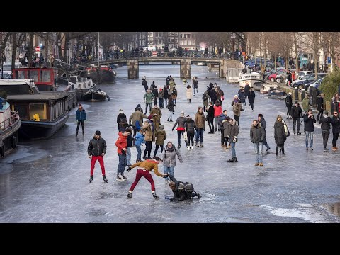 Ice skaters glide over frozen canal in Amsterdam