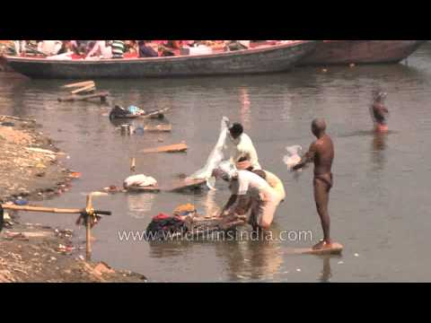 Heavily polluting Ganges river: Washing clothes and bathing in Varanasi