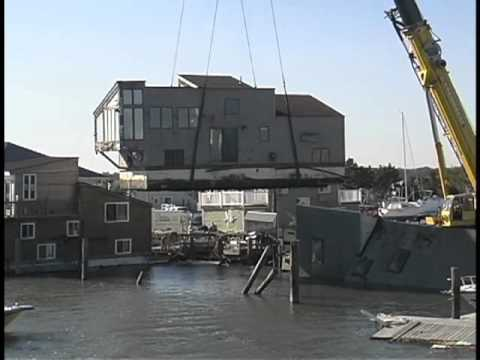 Sea Village Marina, Sea Tow Lifting floating home from the water  after Hurricane Sandy.