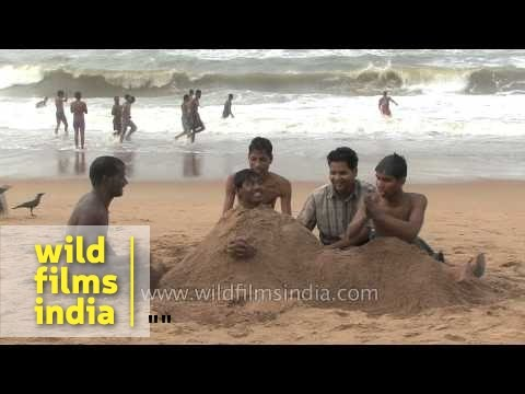 Young boys playing with sand on Puri Beach - Odisha