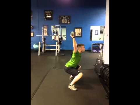 Dan performs an overhead press to squat