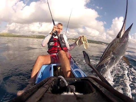 kayak fishing – two kayakers fighting sailfish, sailfish fights back.