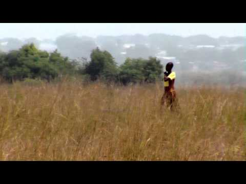 Royalty Free Stock Footage of African woman walking through a field.