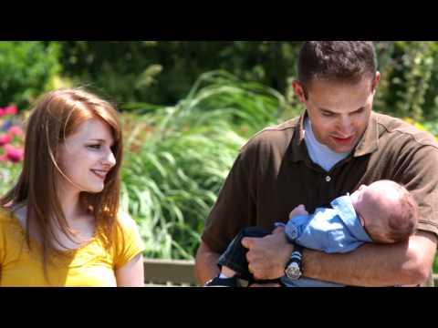 Slow motion shot of a young family walking through beautiful gardens.