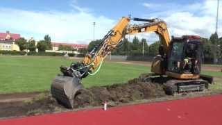 CAT 308D smooths the green carpet on a football field in 2013