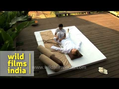 Woman gives body massage to a tourist at a resort in Goa