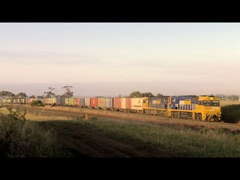 Long Freight Train & Passenger Train Speed Through a Railway Level Crossing - PoathTV