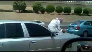 Saudi Man Texting on Hood of a Speeding Car