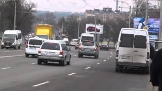 Face slalom cu căruciorul printre mașini