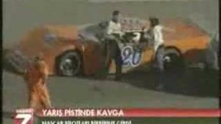 レーシングカーの窓越しに顔面ドロップキックをお見舞いしようとするドライバー