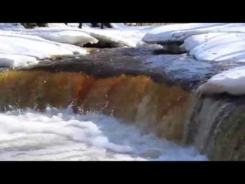 1349 A clear water flowing between the snow covered are a