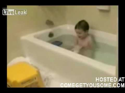 kid pulls cat into bath tub