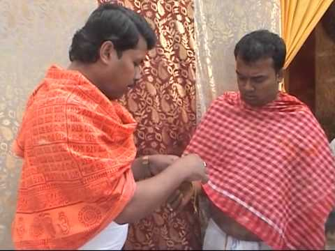 PUROHIT TYING THREAD ON GROOM HAND