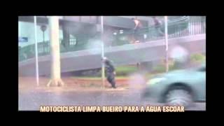 Motociclista limpa bueiro para �gua escoar durante temporal na Capital