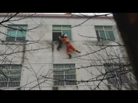 Chinese firefighter grabs woman about to jump off building