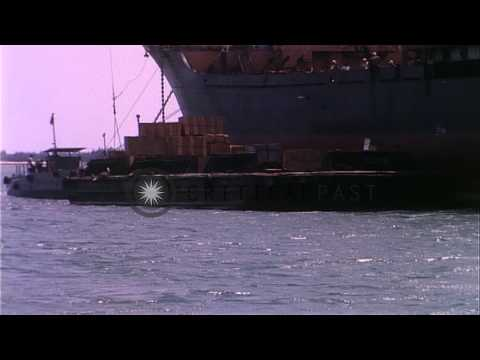 Offload of supplies onto barge from merchant ship at harbor in Da Nang. HD Stock Footage