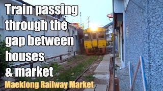Train passing through the gap between houses and market