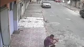 Perro orina a hombre sentado