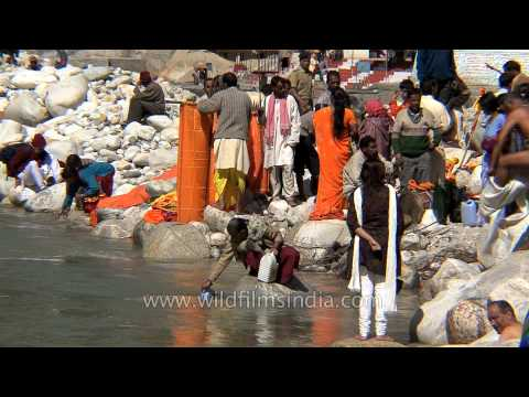 Devotees bathing and filling bottles with holy water of river Ganga in Gangotri