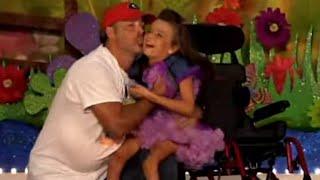 Menina na cadeira de rodas dança com o pai