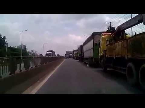 Xe tải xếp hàng chạy trên QL1A.
