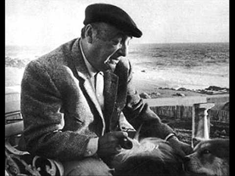 Pablo Neruda in una foto in bianco e nero siede su una sedia avanti alla sua casa in riva al mare