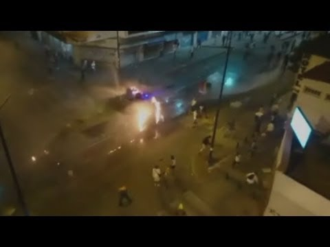 Protesters set fire to a police water cannon in Venezuela