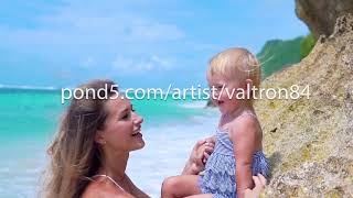beautiful young mother with child of 2 years in her arms walk and having fun on beach. Bali
