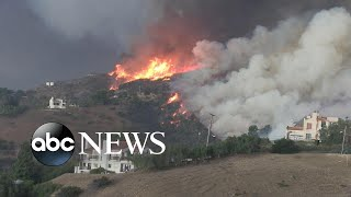 Fast-moving fires force mass evacuations in southern California