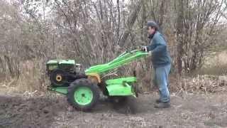 Diesel walk-behind tractor. Work cutter on solid ground.
