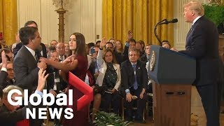 White House aide grabs mic from CNN's Acosta during heated exchange with Trump