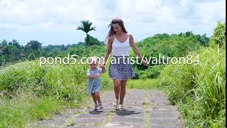 beautiful young mother with child of 2 years in her arms walk through the picturesque countryside