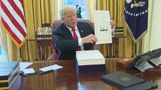 Trump signs tax bill into law