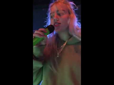 Billie Eilish gives water to a fan who's about to pass out during Ocean Eyes