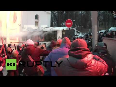 Kiev protesters club prone police officers