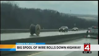 Big spool of wire rolls down highway