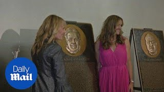 Brandi Chastain stands next to her soccer Hall of Fame plaque