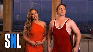 "SNL Host Ronda Rousey Lets Beck ""The Wreck"" Bennett Try His Noggin Lock"