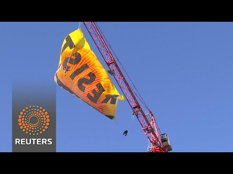 "Anti-Trump protesters unfurl ""Resist"" banner atop D.C. crane"