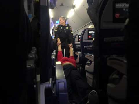شاهد.. شرطي يسحل امرأة داخل الطائرة.. ...