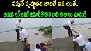 Kodali Nani helps Anil to climb Krishna river bund in floo..