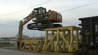 Cat 319D LN climbing onto rail car