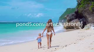 beautiful young mother with child of 2 years walk and having fun on beach. Bali, Indonesia